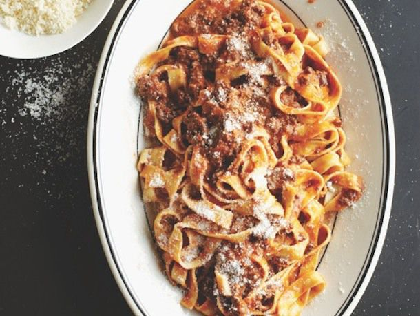 Lamb bolognese tossed with fettucine noodles and sprinkled with freshly grated cheese on a white oval platter.