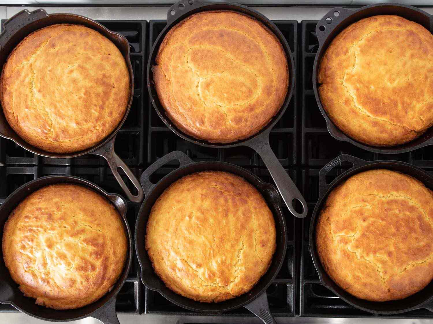 An overhead shot of several cast iron skillets, each containing golden brown cornbread; the differences from skillet to skillet were impossible to discern.