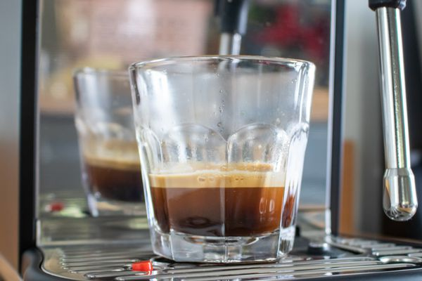a clear glass with a double espresso shot from the Breville Bambino Plus espresso machine
