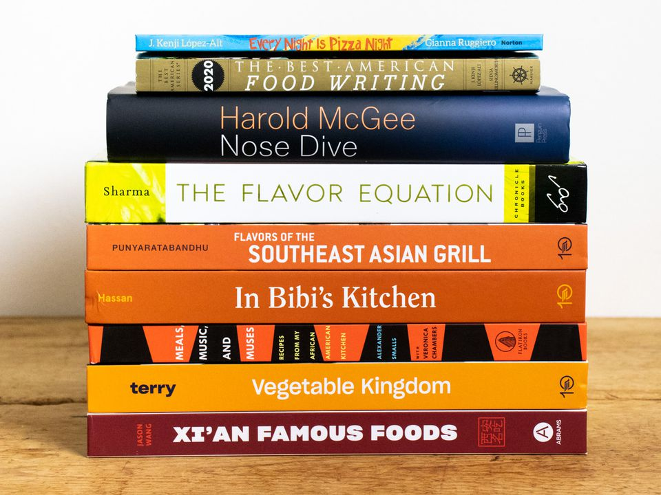 a stack of cookbooks on a wooden tabletop
