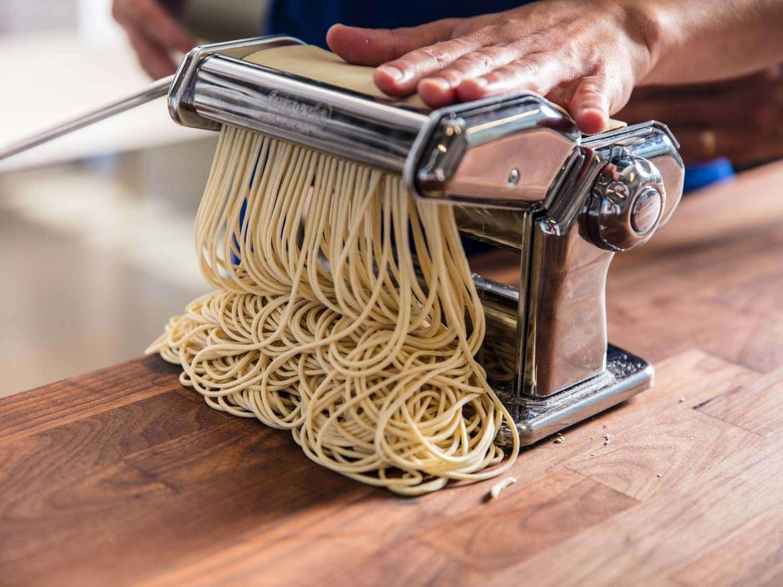 Pasta cutter cutting ramen dough sheets into noodles