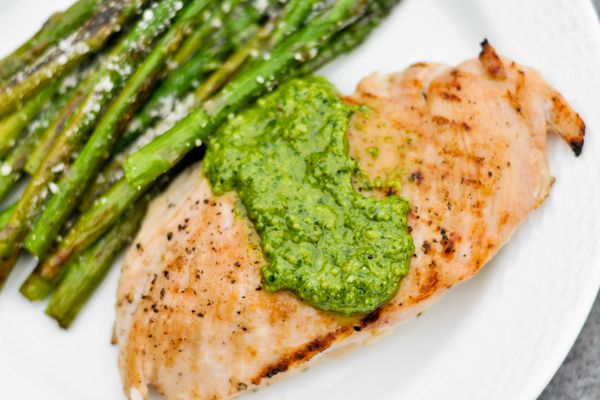 Grilled chicken breast on a plate with a dollop of green sauce and a side of asparagus