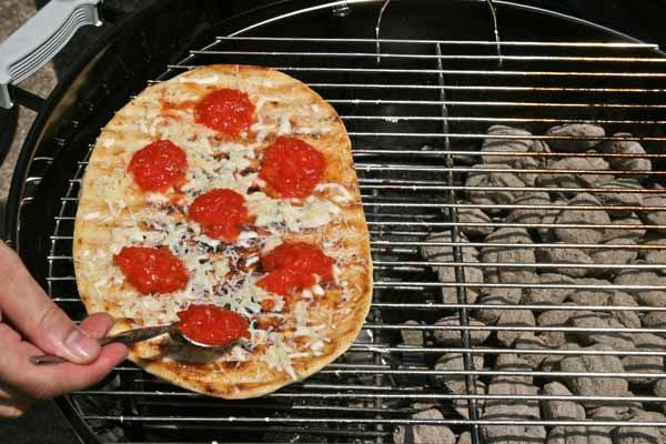 adding sauce to grilled pizza dough