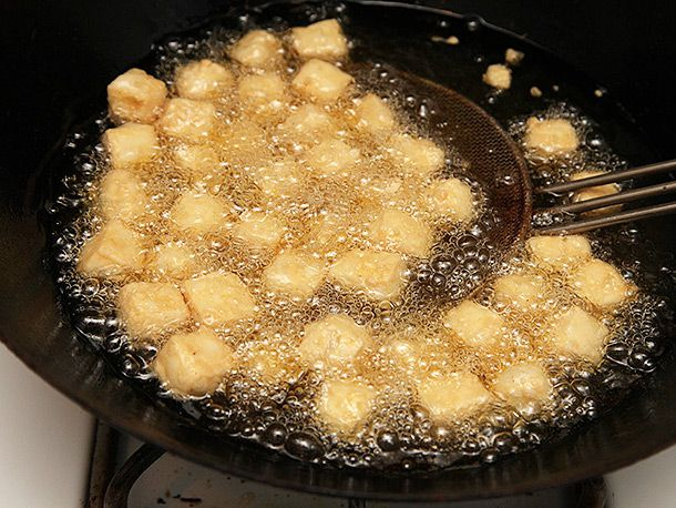 Frying tofu cubes in a wok.