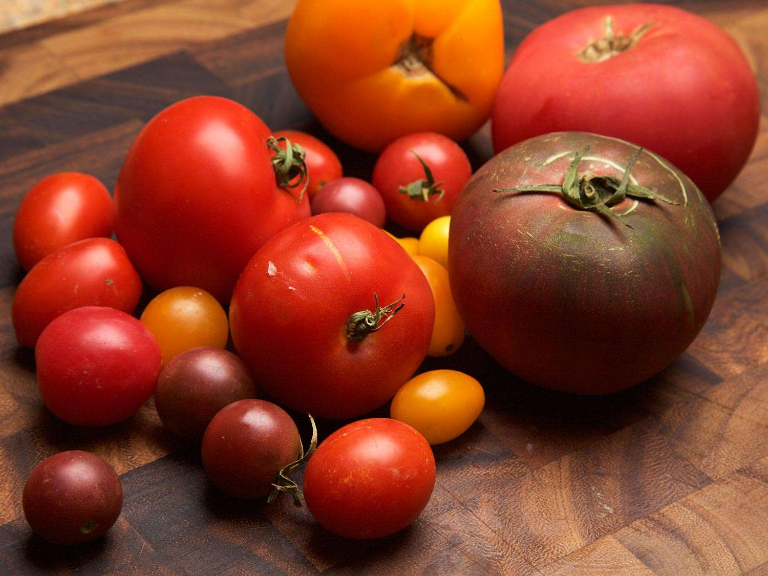 An assortment of ripe tomatoes of different colors and sizes, on a wooden chopping board