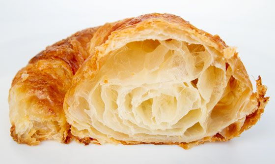 A croissant cut in half to show the layers inside