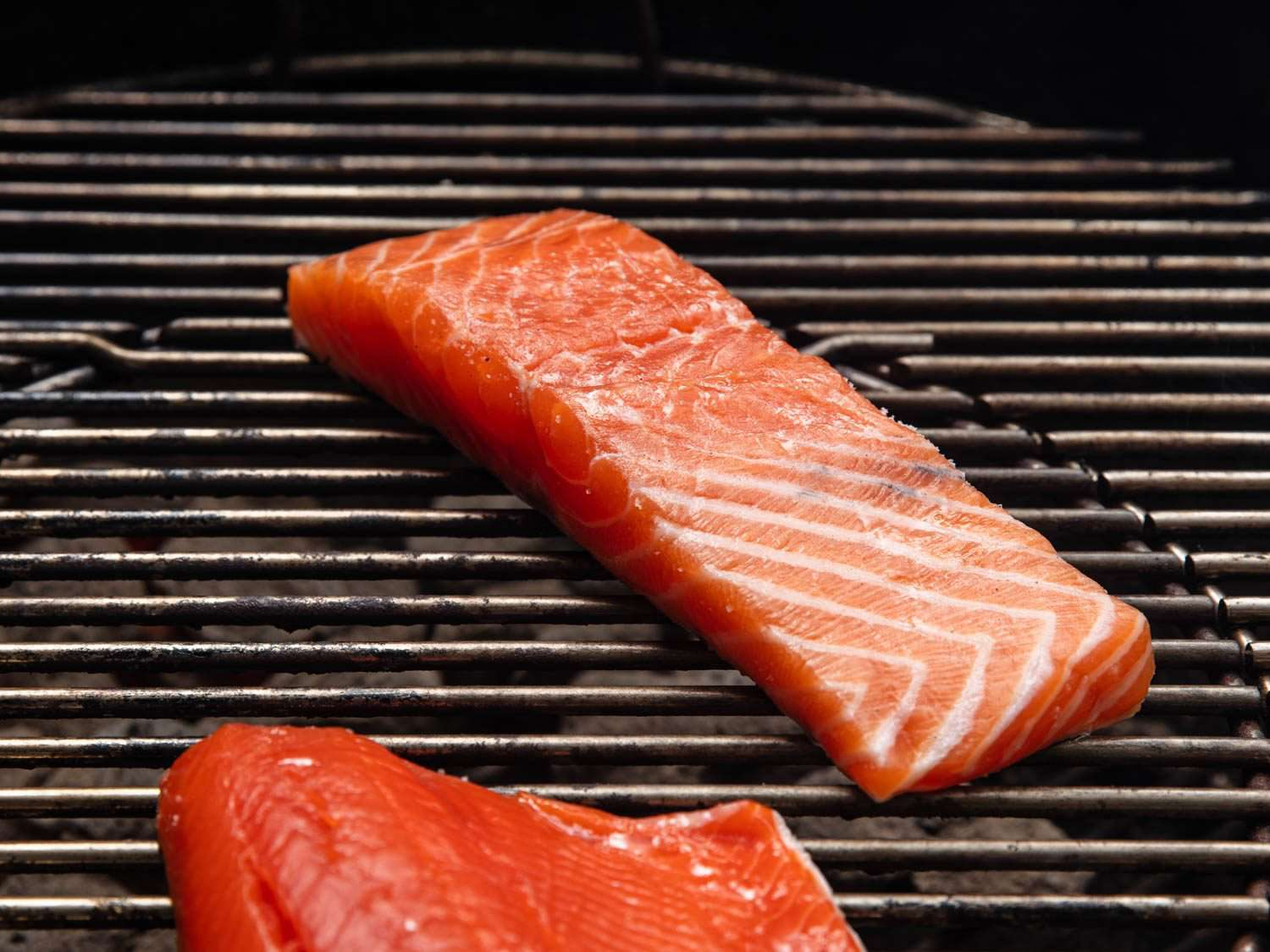 A piece of salmon, still mostly raw, skin side down on the grill.