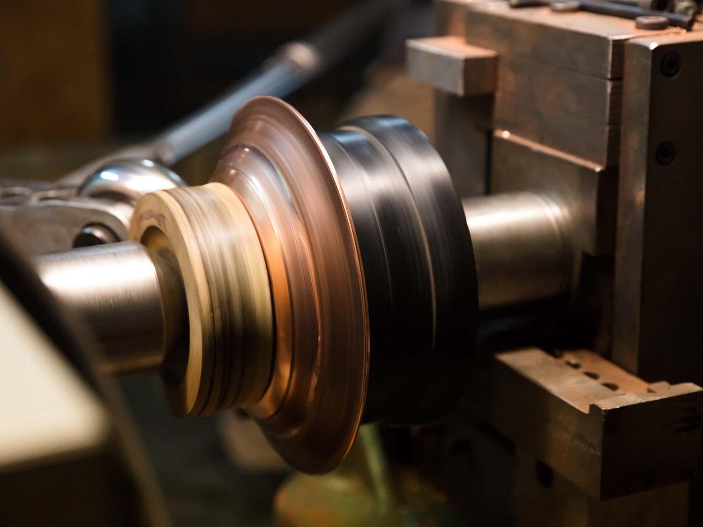 A disc of copper being spun into a saucepan on a lathe