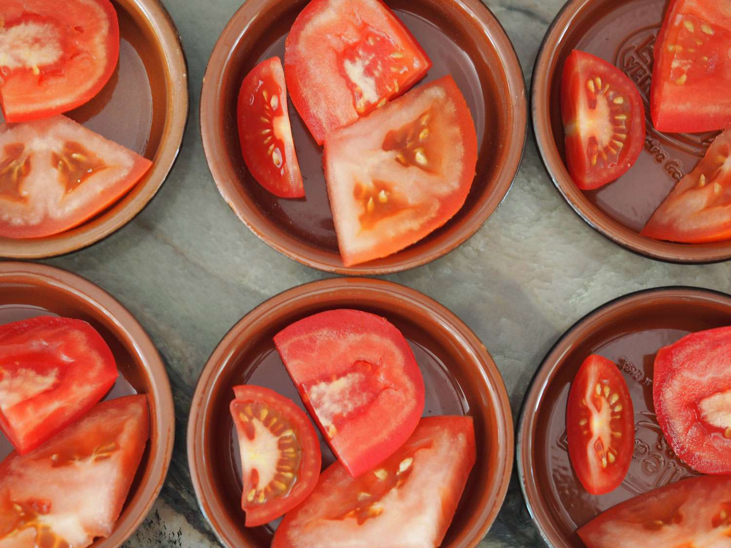 Pieces of tomato divided into various bowls for tasting