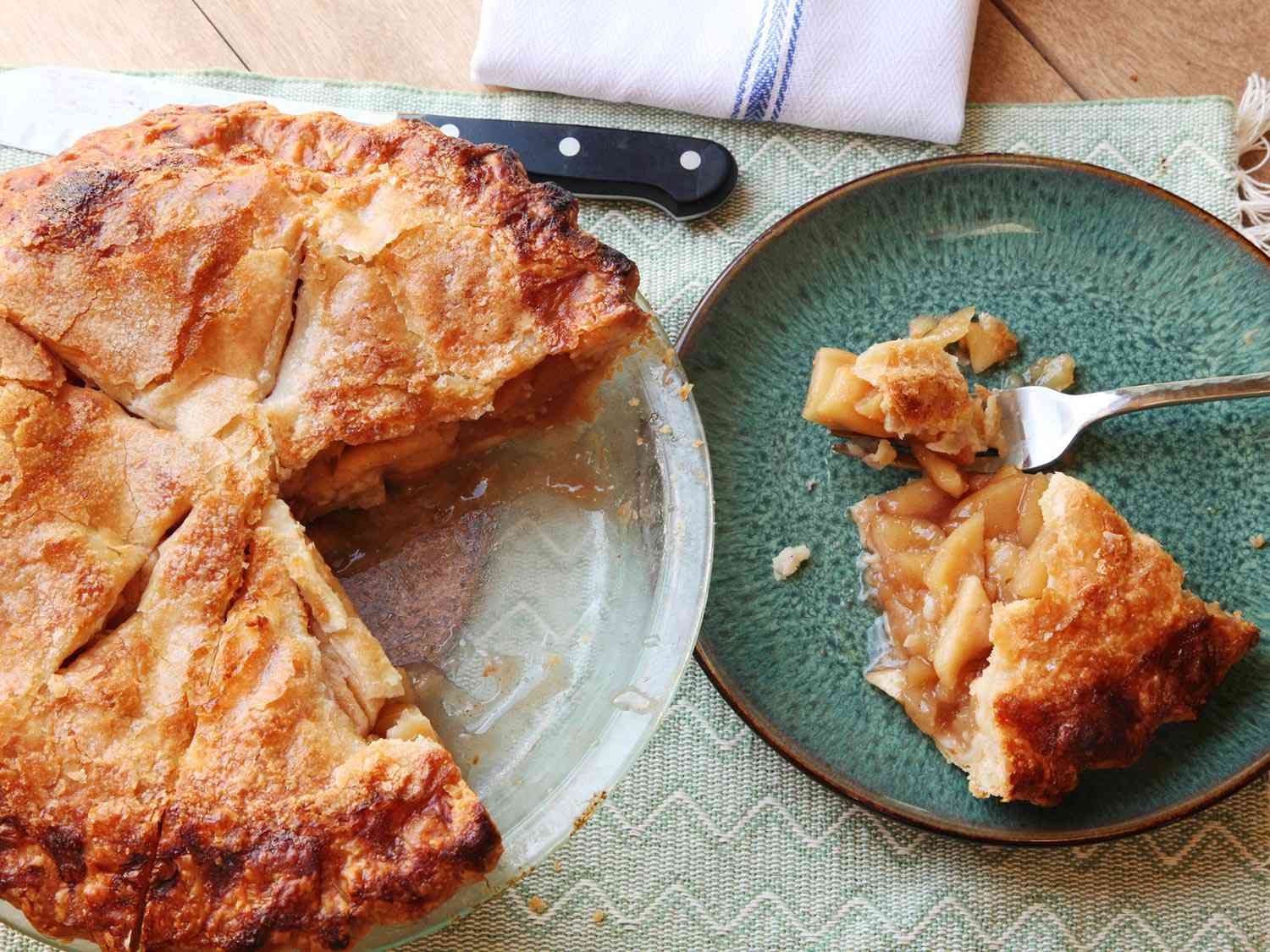 A slice of gooey apple pie on a plate, next to the remainder of the pie in a glass pie dish