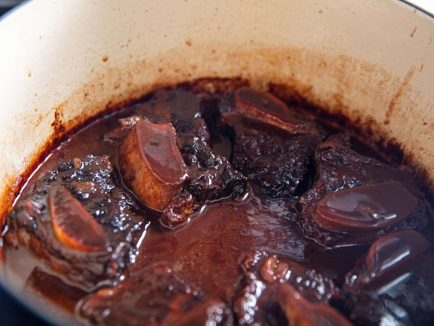 Braised beef short ribs in a Dutch oven with the finished red wine sauce