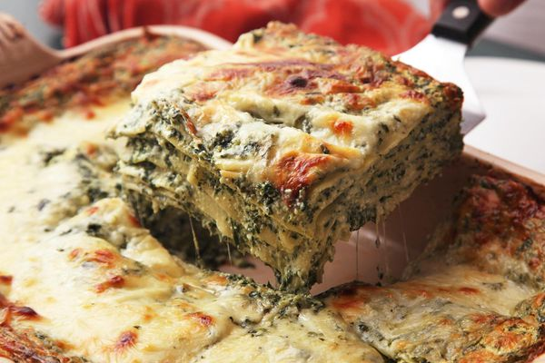 Spinach lasagna in a casserole, and someone lifting a square of the lasagna above the dish with a spatula