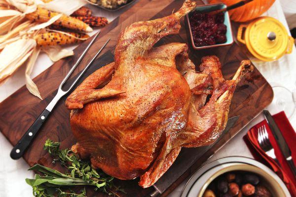 A roast turkey on a wood cutting board.