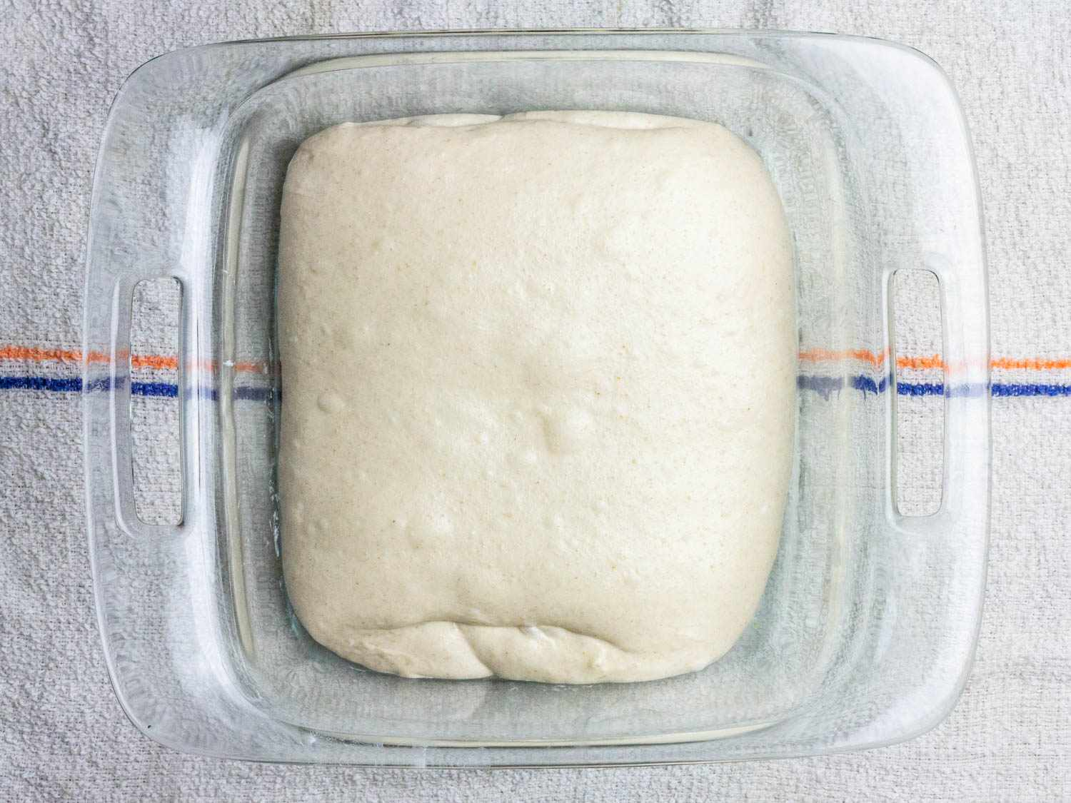 The raw dough for Sourdough bread sits in a square glass baking dish; it looks soft and tender with some visible pockets of air under the surface