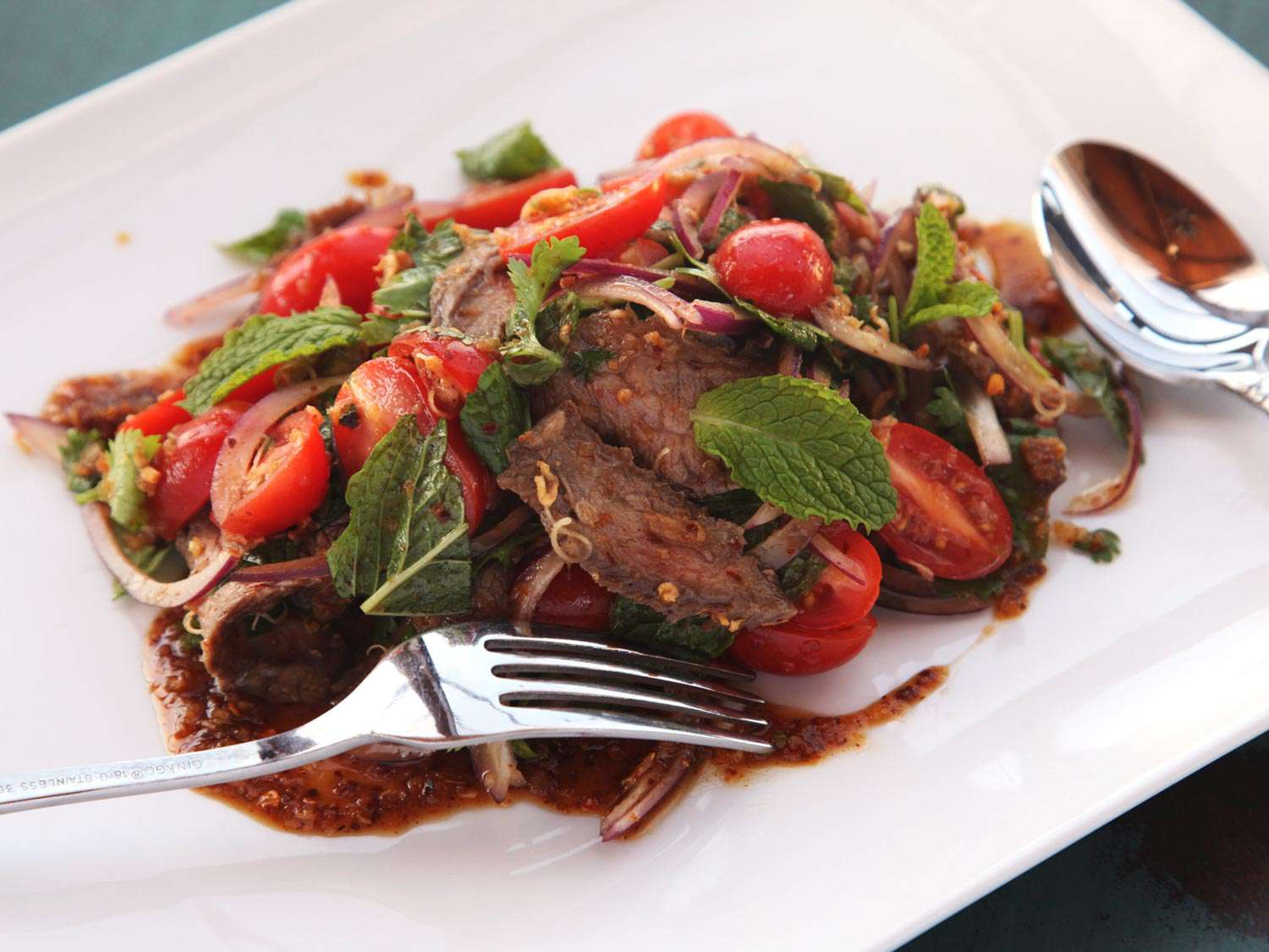 Isan Thai steak salad with tomatoes, onions, mint leaves, and spicy dressing, on a white plate