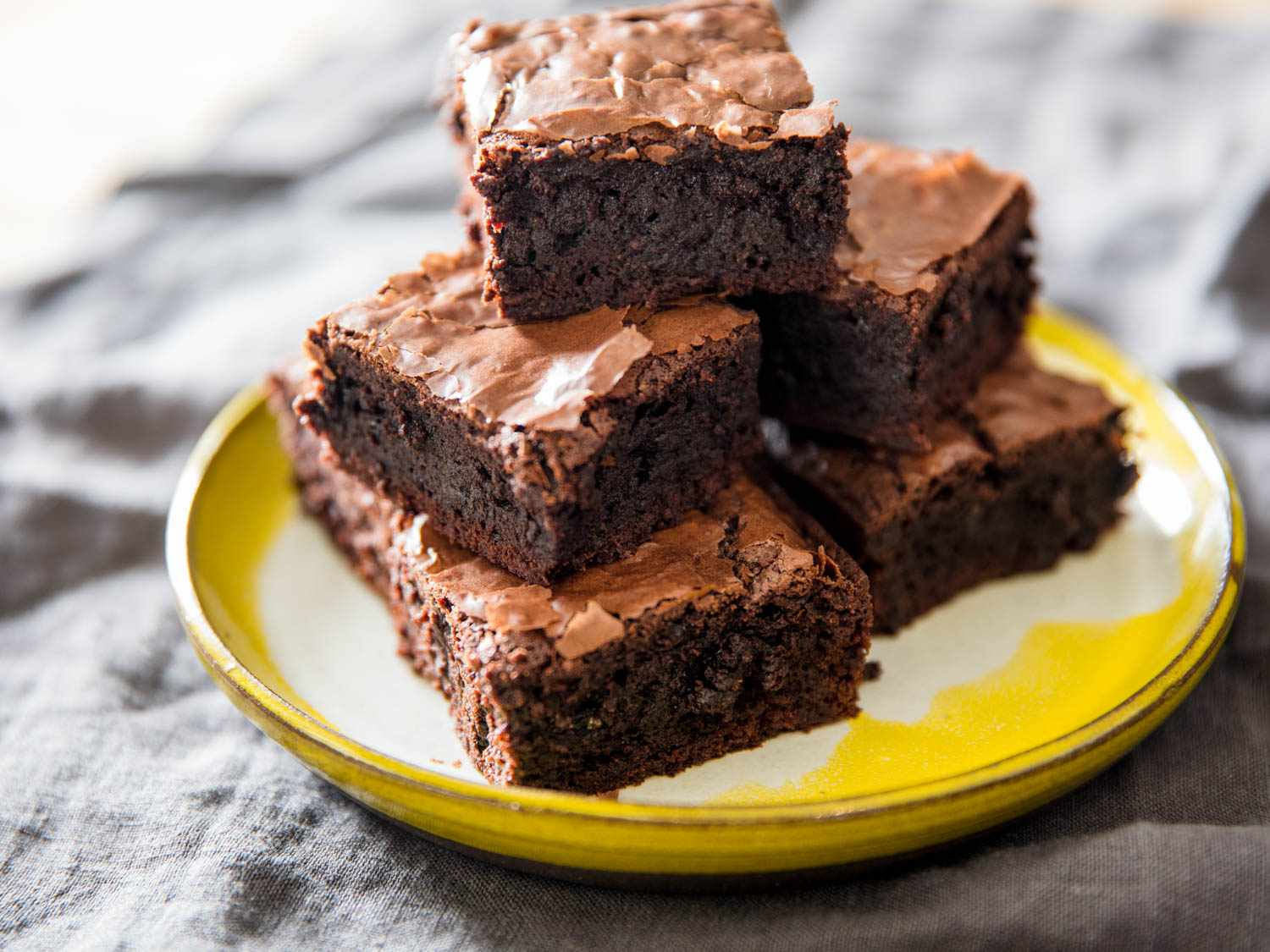 A stack of glossy chocolate fudge brownies on a plate.