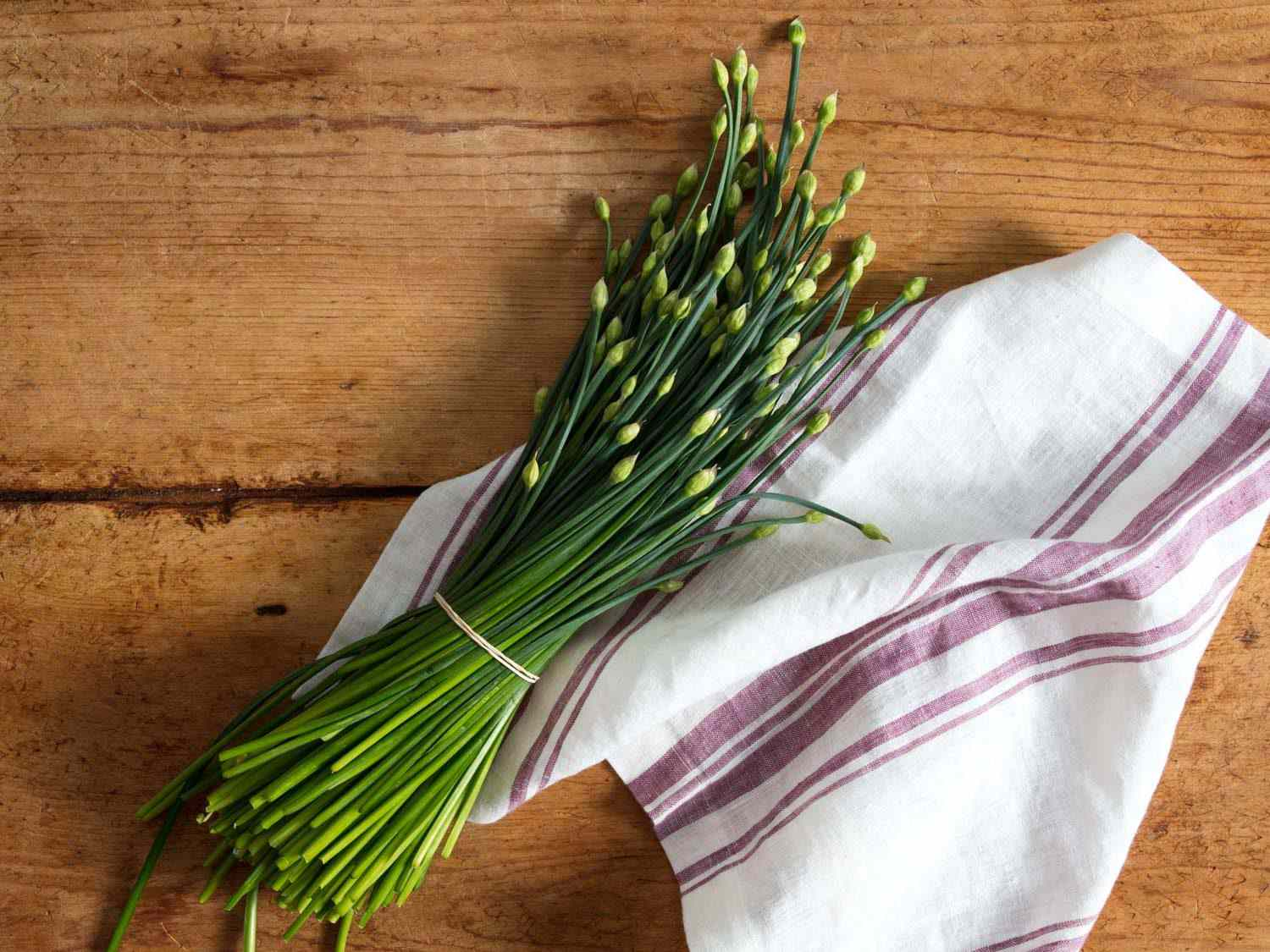 Bundle of flowering garlic chives on a table.