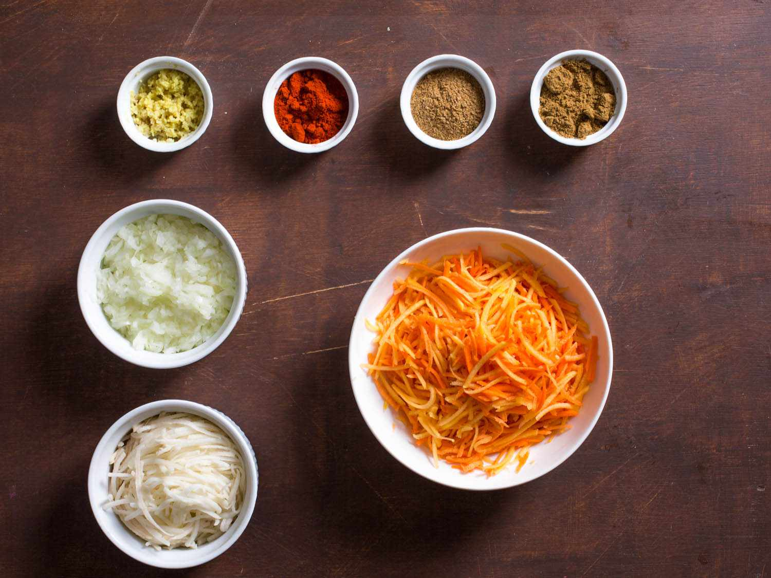 Overhead shot of ingredients for sweet potato, squash, and carrot latkes: shredded carrot, squash, and sweet potato; shredded potato; chopped onion; fresh ginger; paprika; cumin; and coriander