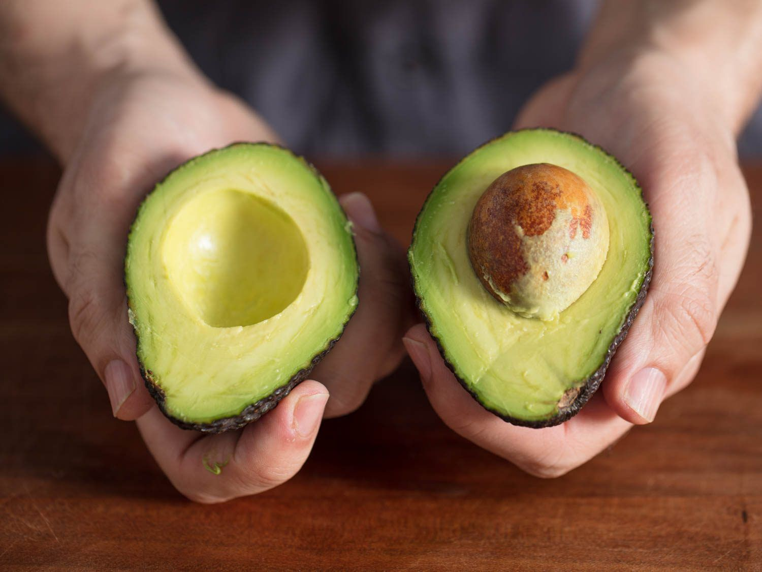 Two hands displaying the two halves of a split ripe avocado
