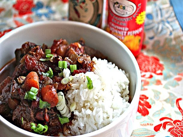 Jamaican Beef Stew in a bowl with white rice and green onions sprinkled on top