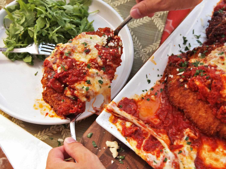 Transferring chicken parmesan onto dinner plate