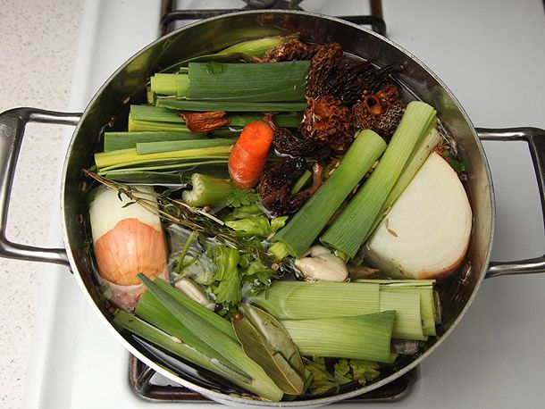 An overhead view of a stockpot filled with leeks, onions, carrots, and more to make homemade vegetable stock.