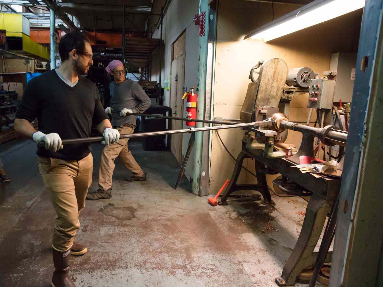 Daniel Gritzer and Jim Hamann work on a lathe to make copper saucepans