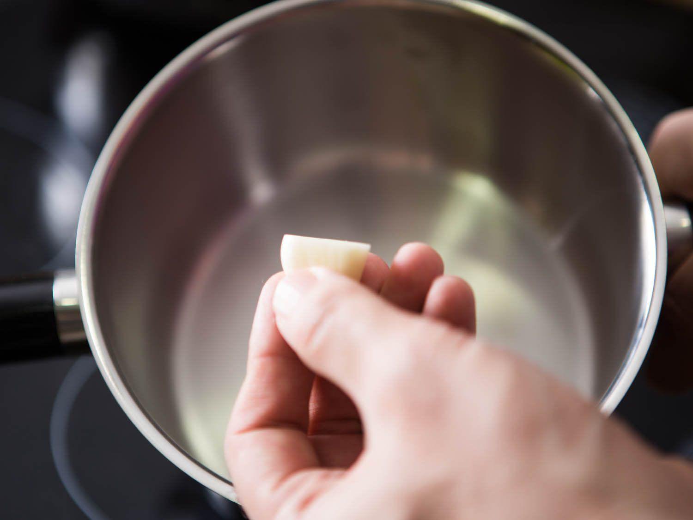 Holding a clove of garlic over a small sauce pot.