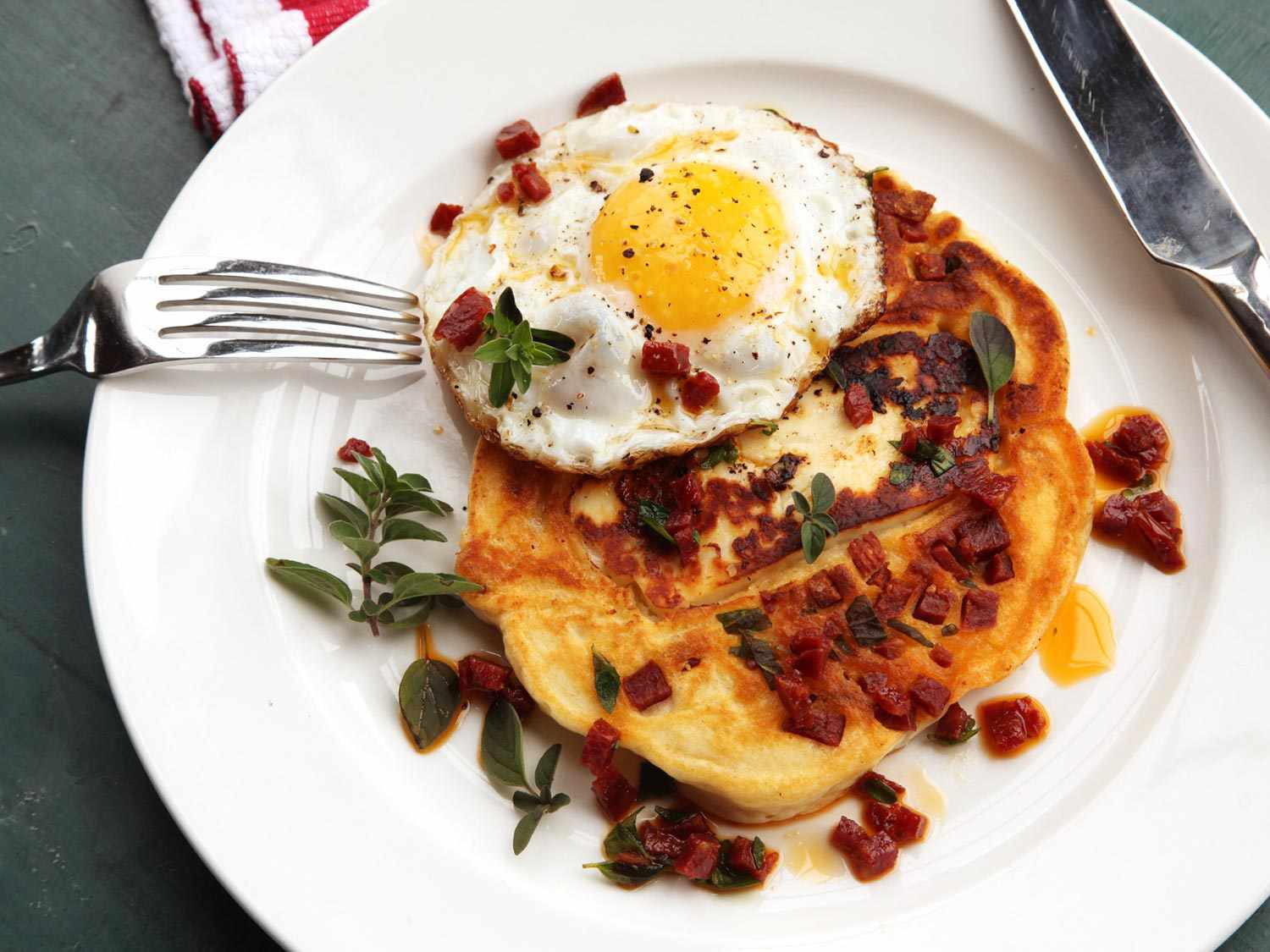A chorizo and halloumi pancake with a fried egg on a plate. The food is garnished with oregano sprigs and there is a fork and knife on the plate.