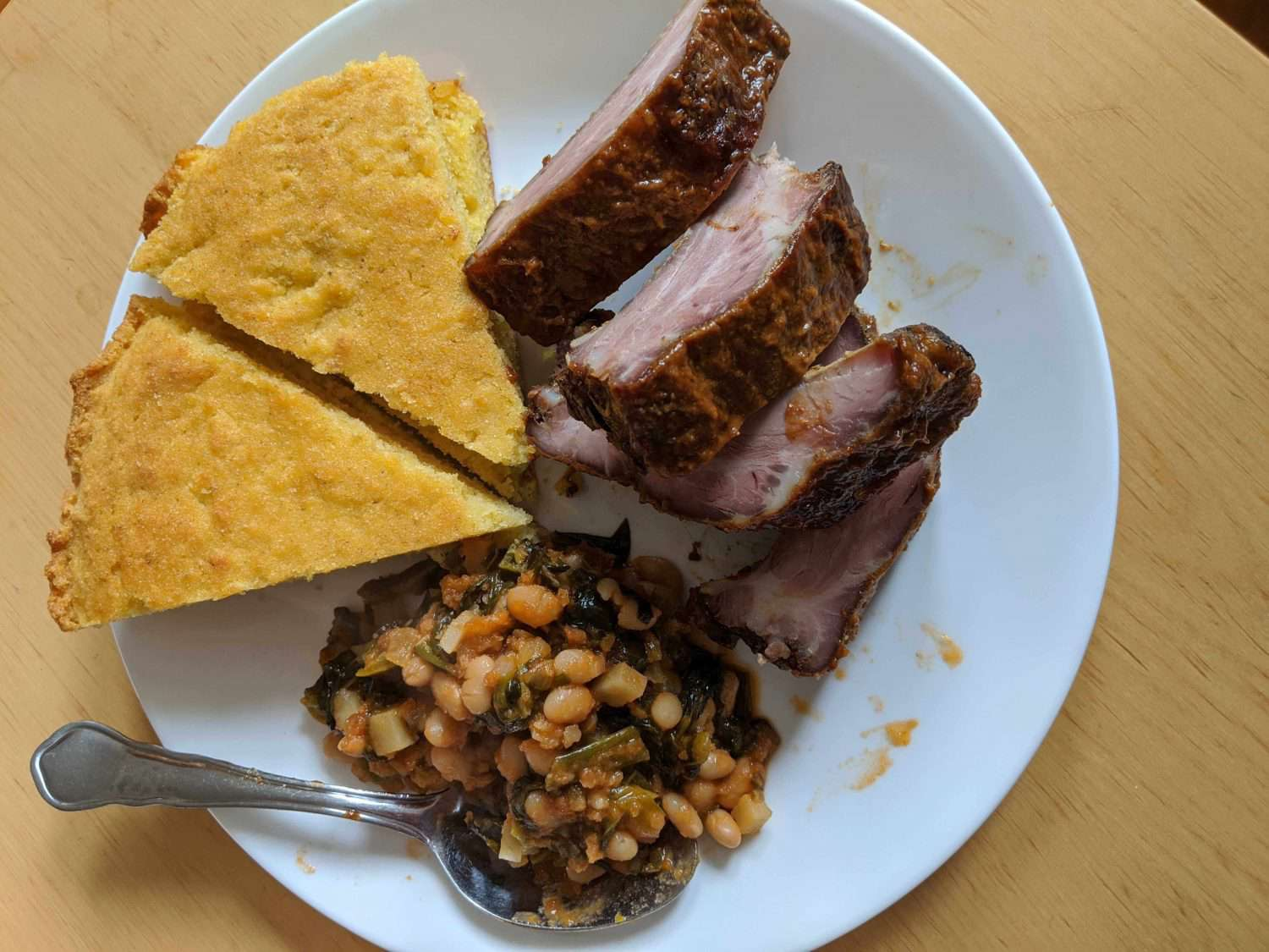 Cornbread, ribs, and beans and greens on a plate