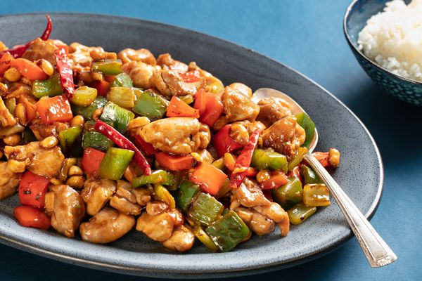Takeout-style kung pao chicken on a grey plate with rice on the side.