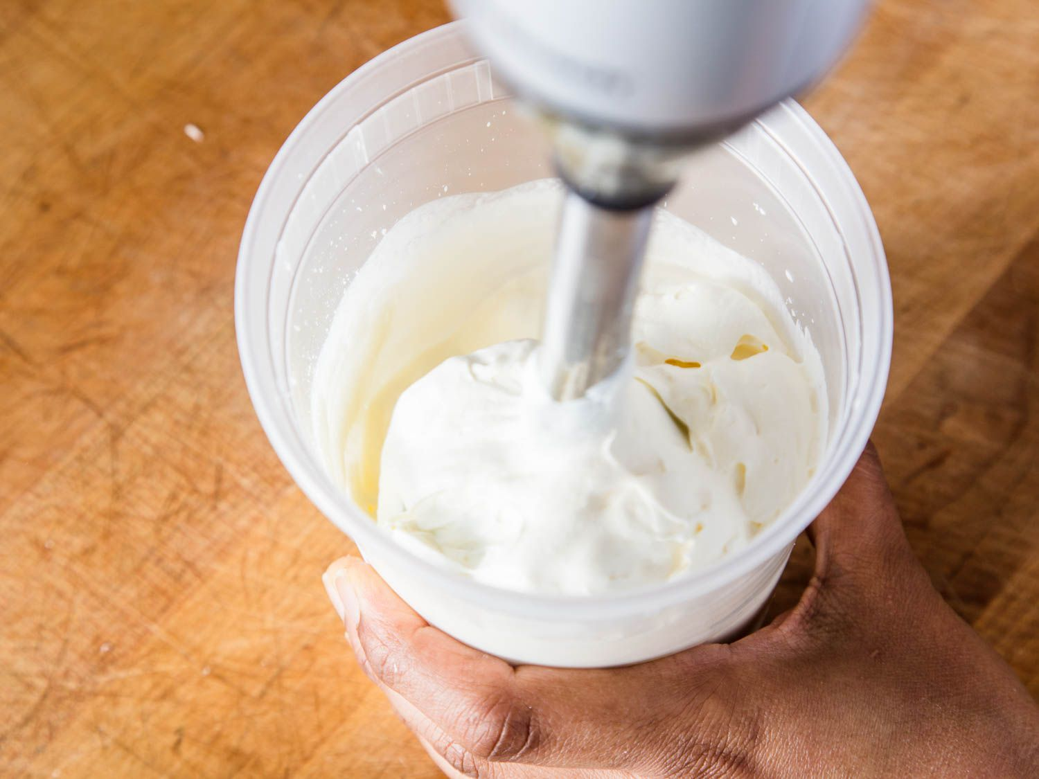 Using an immersion blender to whip cream in a clear plastic container