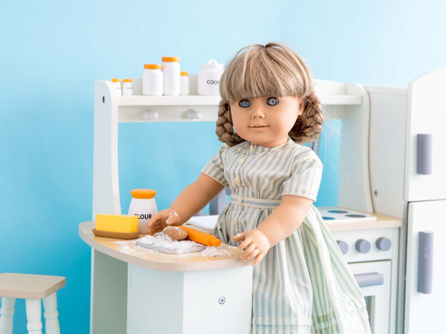 A Kirsten doll rolling out dough for St. Lucia buns in a white doll kitchen