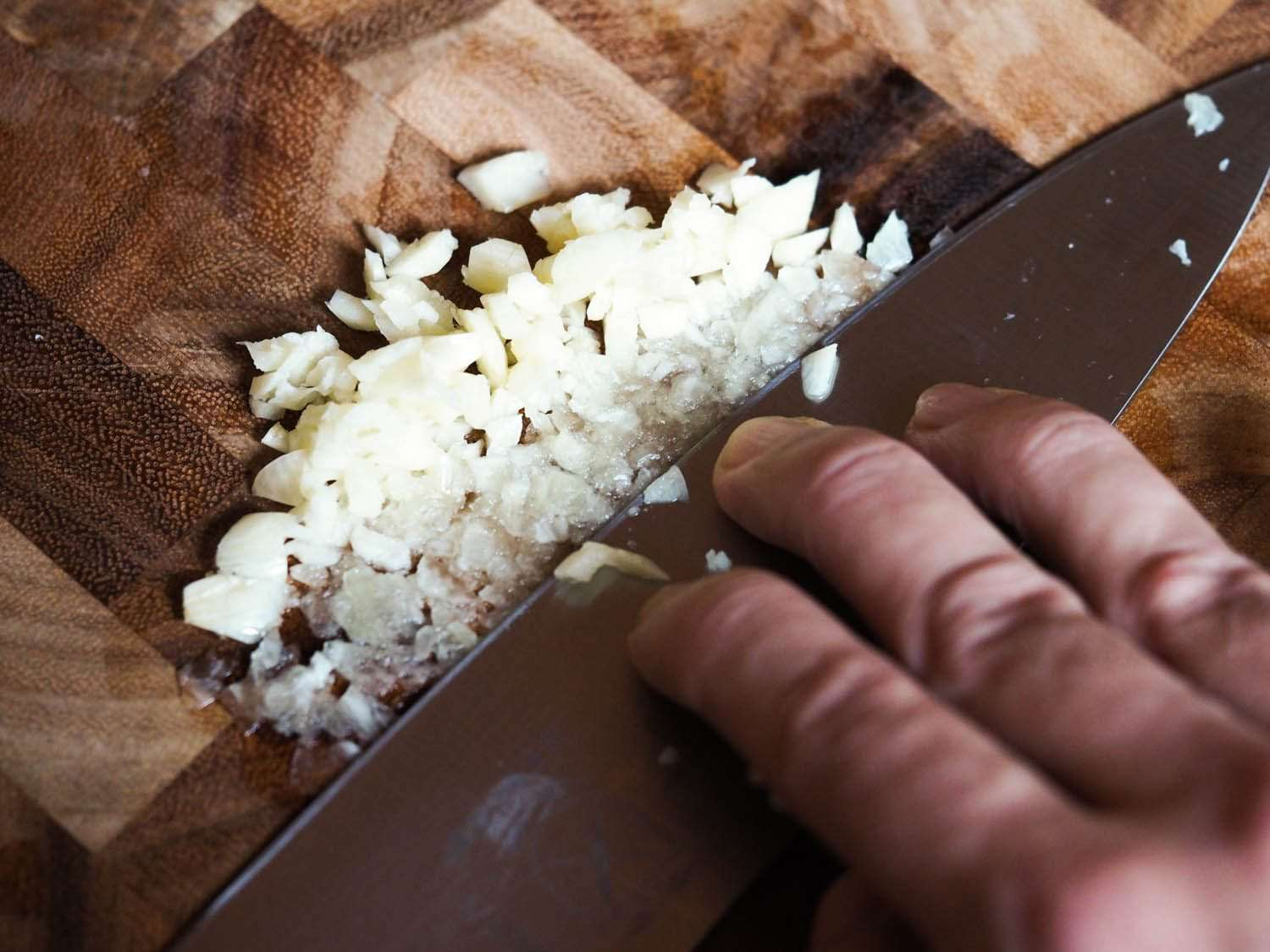 Crushing garlic with the side of a knife.