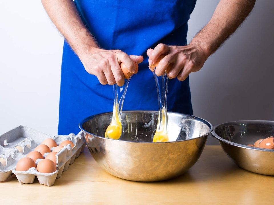 person cracking eggs into bowl