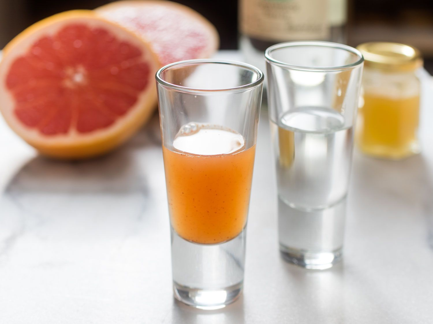 A shot glass of grapefruit-chipotle-honey sangrita, with a shot of tequila in the background
