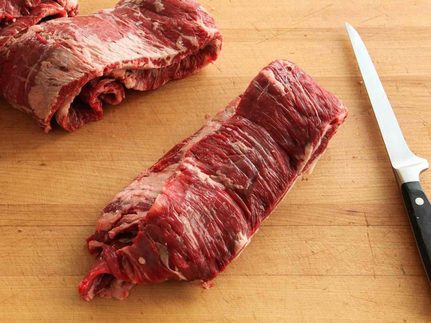 Skirt steak on a wooden cutting board next to a knife.