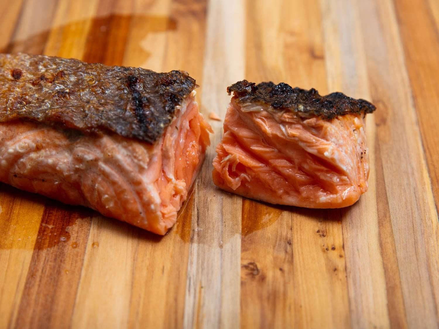 A piece of grilled salmon on a cutting board, showing a cross section to reveal a medium doneness, neither dry and well done nor rare.