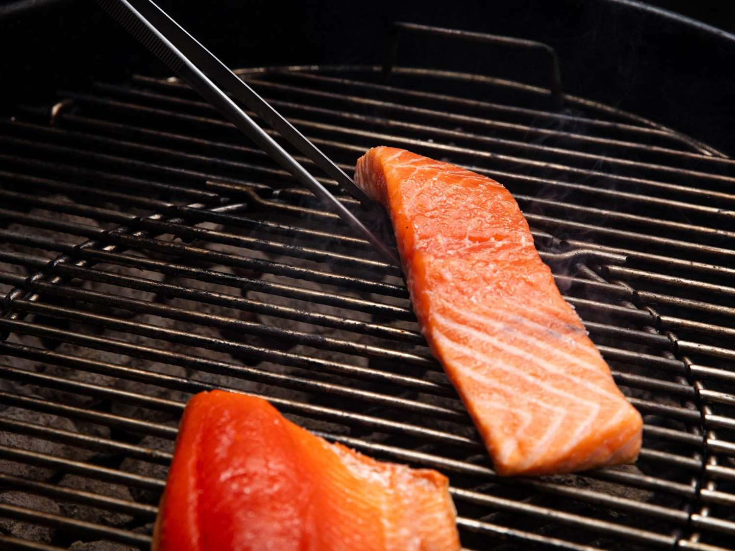Using the thin prongs of culinary tweezers to lift a piece of salmon from below to turn it on the grill.