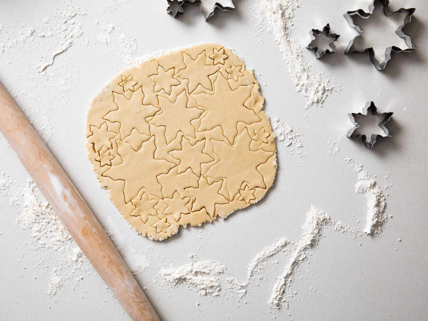 A rectangular piece of sugar cookie dough with snowflake cookie shapes cut into it, and snowflake cookie cutters nearby