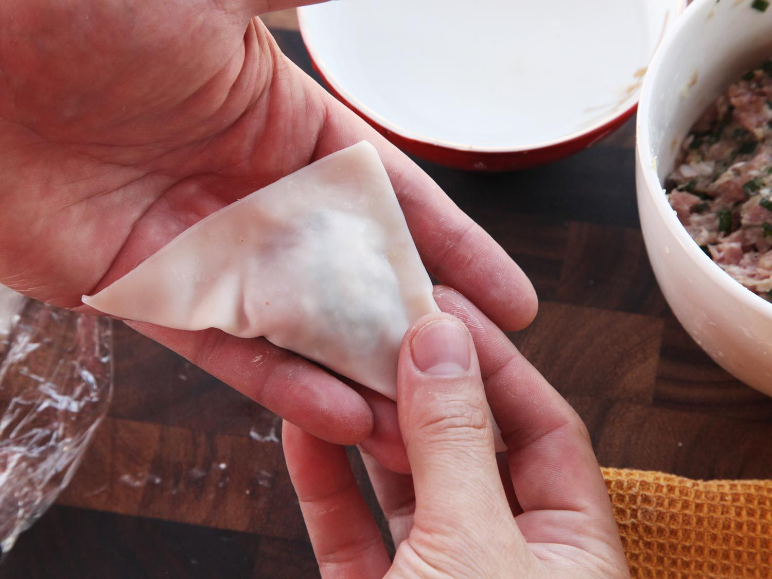Folding over wonton wrapper to form triangle and sealing edges