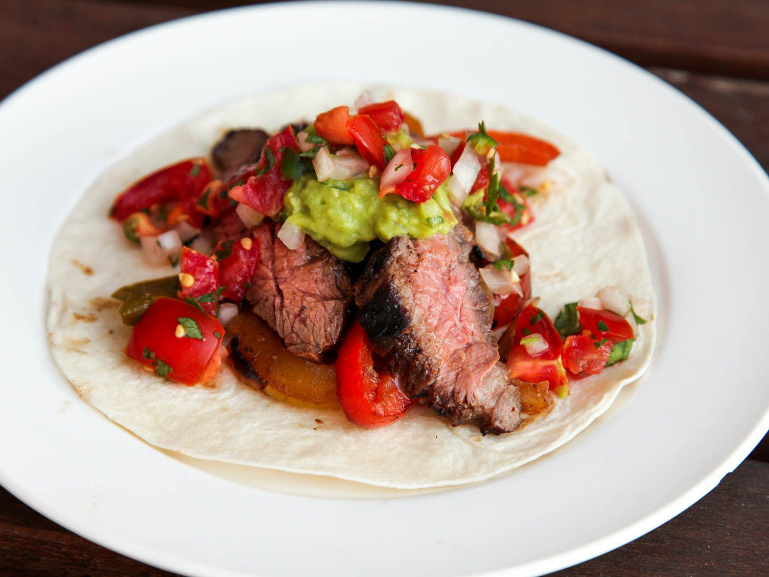 A white plate holding a flour tortilla topped with steak fajitas, grilled peppers and onions, guacamole, and pico de gallo.