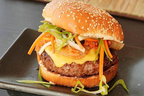Kimchi cheeseburger on a black rectangular plate.