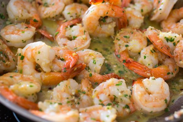 Shrimp scampi in a pan with lots of butter, garlic and parsley.