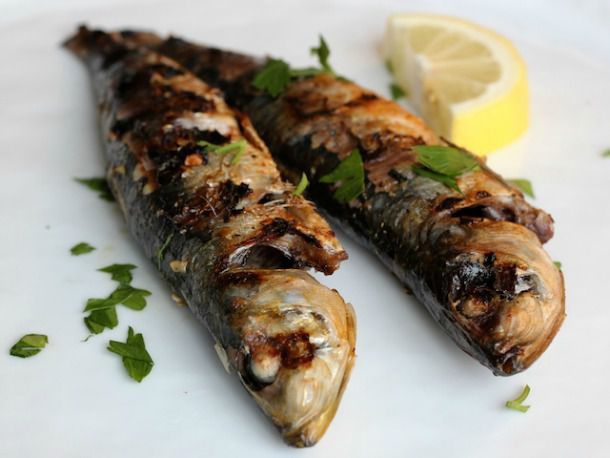Grilled sardines seasoned with lemon, parsley, garlic, and paprika on a white plate.