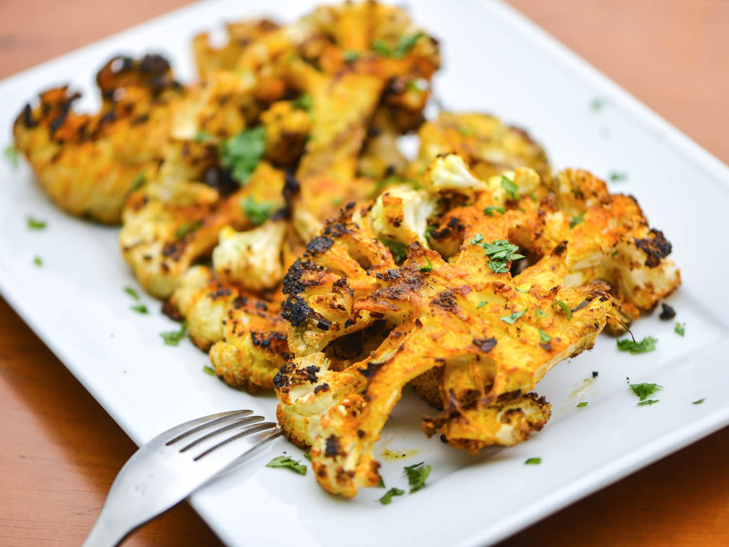 Grilled spiced cauliflower sprinkled with chopped herbs, on a white serving platter