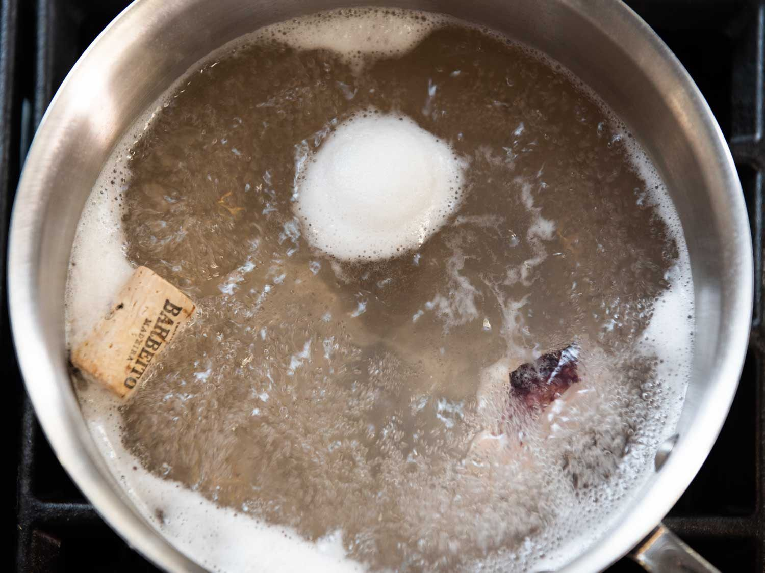 Looking down into a boiling pot on the stovetop, with a piece of octopus and a cork in the water.