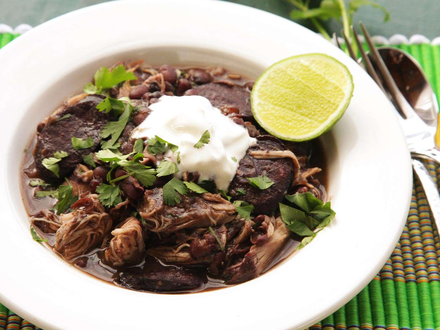 A bowl of Quick and Easy Pressure Cooker Chicken and Black Bean Stew with a lime wedge and a dollop of sour cream.