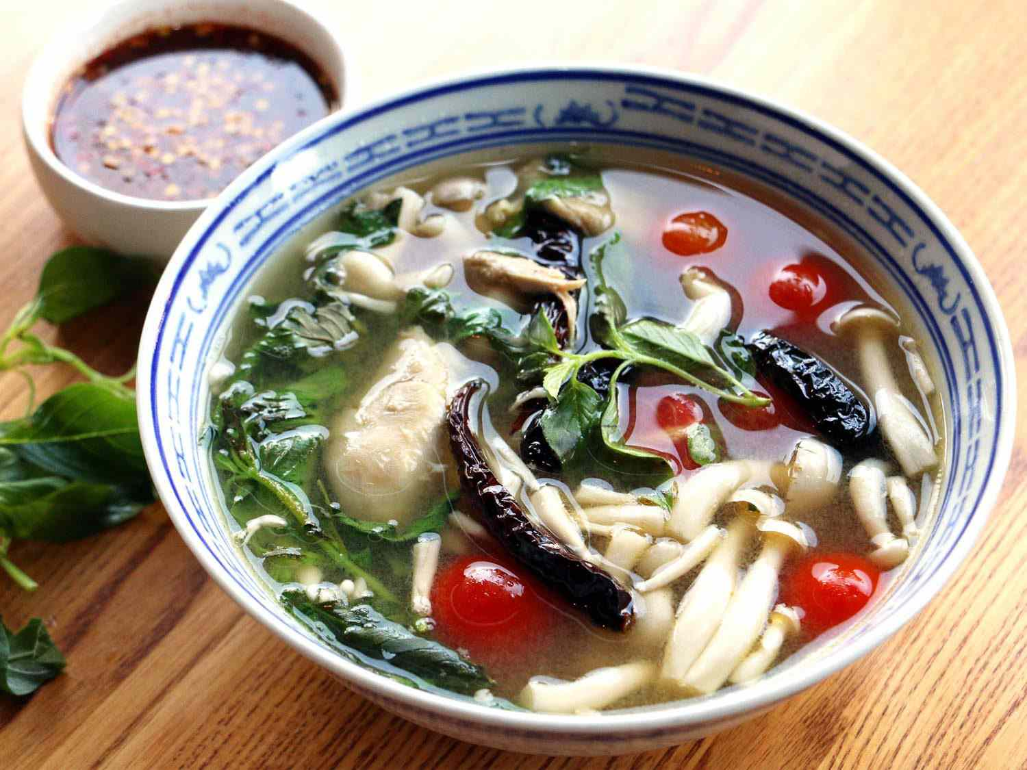 A blue and white bowl of khao soi (wide rice noodles, tomatoes, mushrooms, and greens in a chicken broth) next to a small bowl of chili sauce