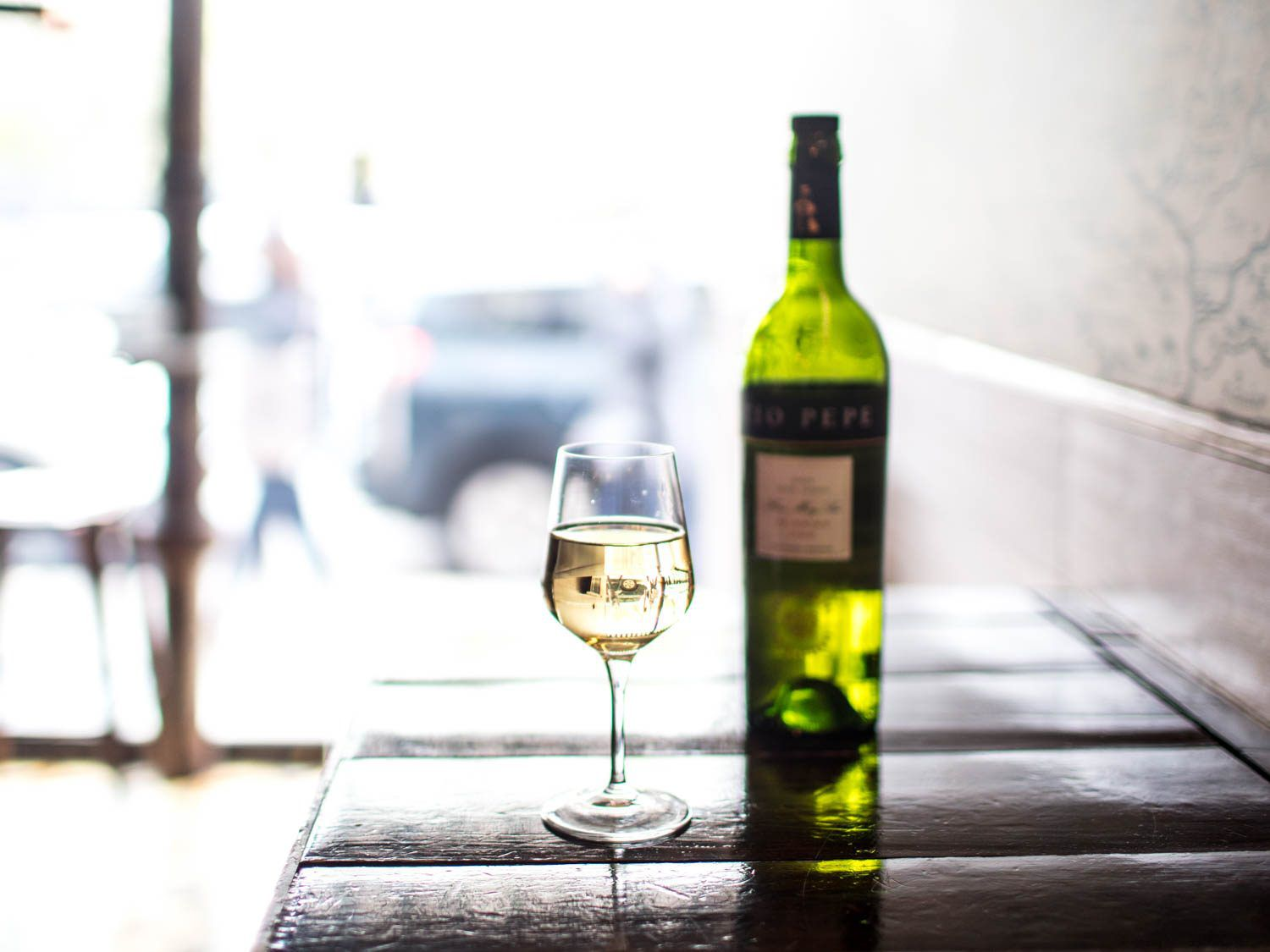 A wineglass of light-colored Fino sherry, with a bottle in the background